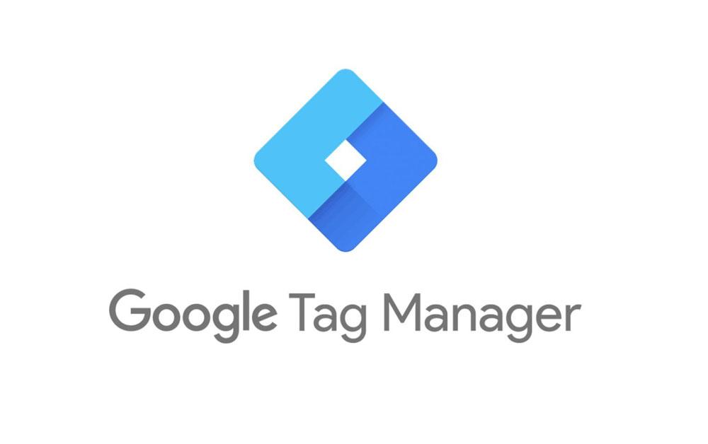 Questa immagine è semplicemente il logo di Google Tag Manage. Il logo ha un design estremamente semplice e chiaro: un quadrato dai bordi molto spessi che vanno a formare un altro quadrato bianco al centro. La metà destra del quadrato ha una tonalità di colore più scura rispetto alla metà sinistra, il quadrato è ruotato verso destra e quindi proseggia sull'angolo inferiore destro formando un rombo.