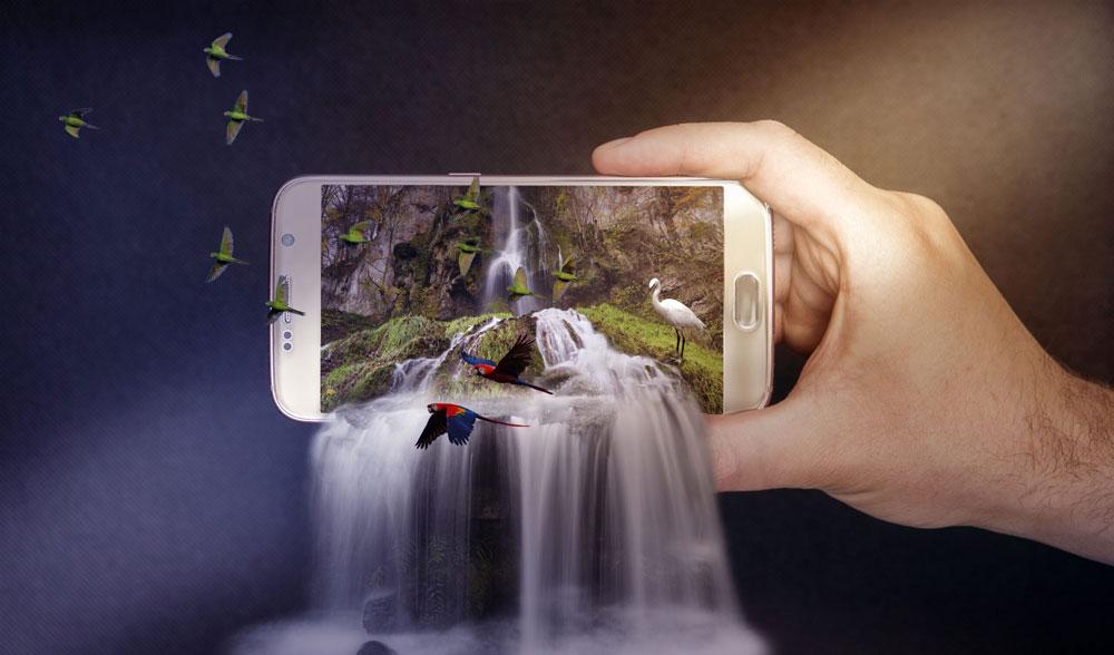 Abbiamo scelto questa foto per rappresentare l'aspetto grafico della Realizzazione siti web in quanto è un bellissimo esempio di fotoritocco/fotomontaggio di una foto. Il soggetto della foto è uno smartphone posto orizzontalmente con la parte superiore posizionata a sinistra, con una mano che sorregge la parte inferiore dello smartphone, in cui abbiamo un paesaggio con una parete rocciosa ed una cascata che fuoriesce dal bordo dello schermo smartphone verso la parte inferiore della foto. All'interno dello schermo, in prossimità del bordo inferiore dello smartphone, vi è un airone bianco che osserva la cascata mentre, di fronte ad esso, uno stormo di uccelli sta attraversando lo schermo uscendo dall'estremità dello schermo e proseguendo in alto.