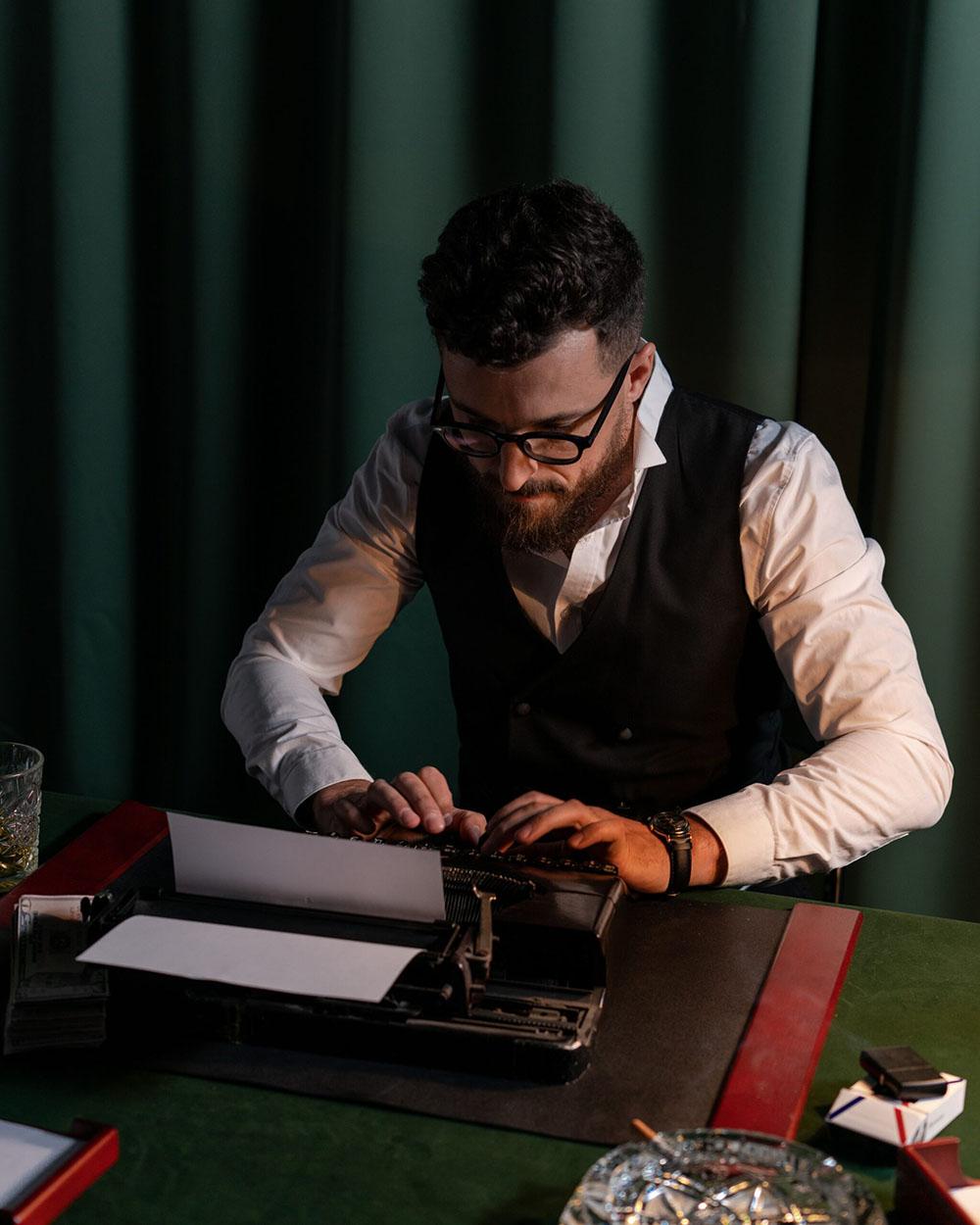 Abbiamo scelto questa foto per rappresentare l'aspetto relativo alla scrittura di testi nella Realizzazione siti web in quanto rappresenta perfettamente la creatività necessaria alla scrittura di un testo adeguato. Il soggetto della foto è un umo con una camicia bianca e ed un panciotto nero impegnato a scrivere con una vecchia macchina da scrivere.